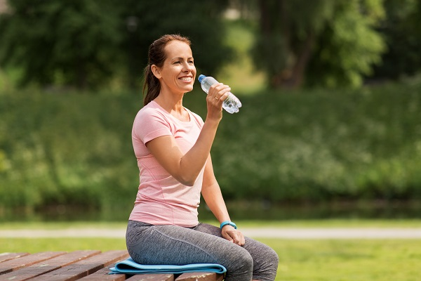woman drinking water outside
